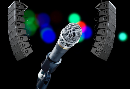 loud speakers: Close up of microphone on dark background with colored spotlights and speakers