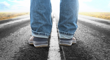 Close up of feet of man on long straight asphalt road photo