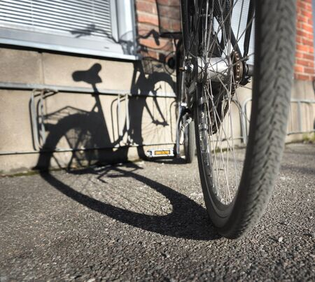rack wheel: bike parked in bicycle rack casting shadow in bright evening light