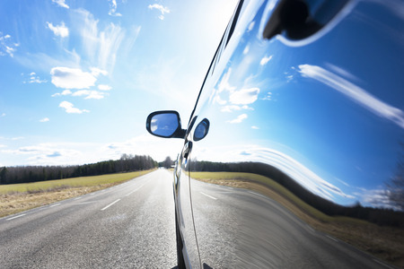 car on the road: Blue sky with clouds and asphalt road reflected in side of car