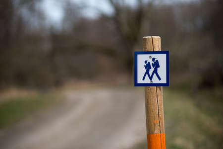 ruck sack: Pole with sign showing a walking path in scandinavian forest Stock Photo