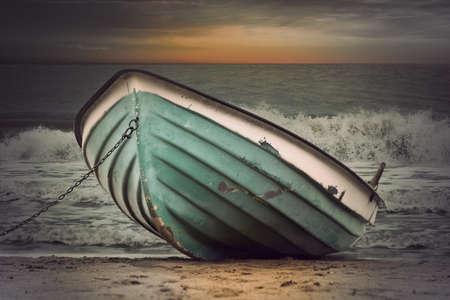 mare agitato: Ormeggiato barca a remi verde in mare agitato al tramonto, stile vintage