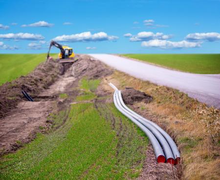 農村地域におけるブロード バンドの接続のためのケーブルを掘るために使用地球掘り 写真素材