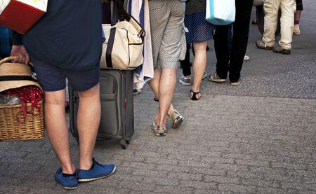 file d attente: Pieds de personnes avec bagages dans des vêtements décontractés attendant patiemment en ligne Banque d'images