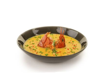 safran: Black bowl with yellow seafood soup and lobster swiming in the middle
