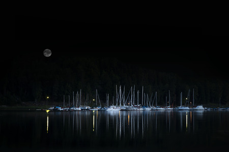 Evening shot of yachts and other small boats moored by small island in Swedish archipelago photo