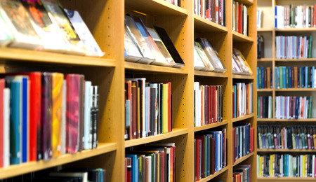 Shelves with many books in bookcases in library