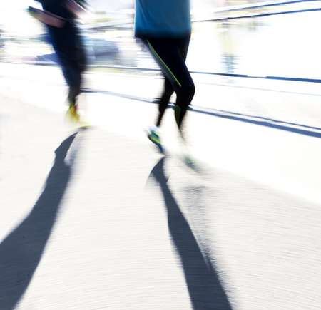 joggers: Two back lit joggers in blurred motion in bright sunshine casting long shadows