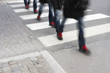 shoe laces: Young man in sneakers with red shoe laces in blurred motion crossing street Stock Photo