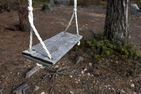 lonliness: Empty vintage wooden swing with big tree in background