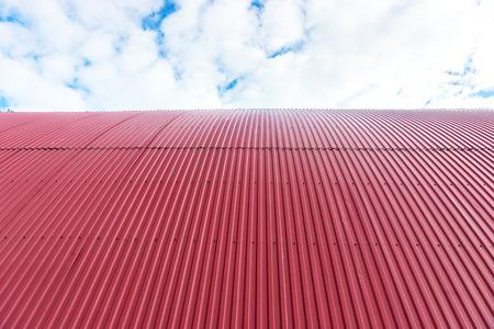 Rooftop von gekrümmten roten Wellblech auf blauem Himmel mit Wolken Standard-Bild - 40117463