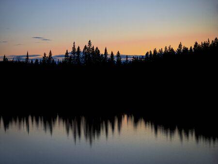 naranja arbol: Lago escandinavo con la silueta de los �rboles refleja en el agua en la noche con el cielo de color naranja y azul
