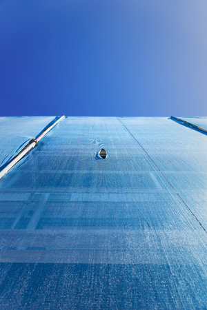 ange: Low ange view of building with scaffolding draped in blue debris netting with small hole on blue sky Stock Photo