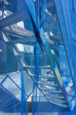 debris: Scaffolding with metal ladder draped in blue debris netting Stock Photo