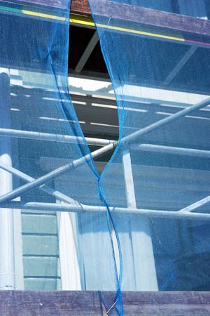 debris: Scaffolding draped in blue debris netting with gap