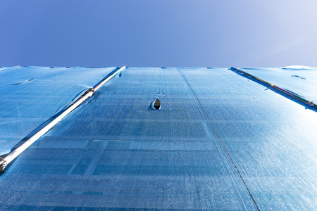 ange: Low ange wiew of building with scaffolding draped in blue debris netting with small hole on blue sky Stock Photo