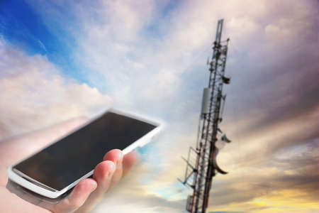 wireless telephone: Hand holding white mobile phone aiming at telecommunication tower on blue sky in background