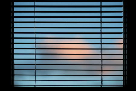 venetian blind: Blue sky with pink clouds seen through window with silhouette of venetian blinds Stock Photo