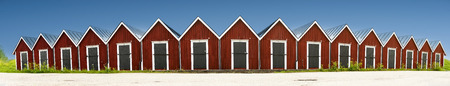 nautical structure: Panoramic view of row of traditional red wooden boathouses on blue sky in summer in small Swedish town
