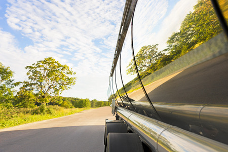 tanker truck on road with reflection of trees in metal