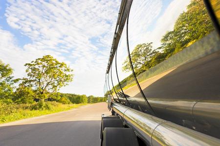tanque: camión cisterna en la carretera con la reflexión de árboles en el metal Foto de archivo