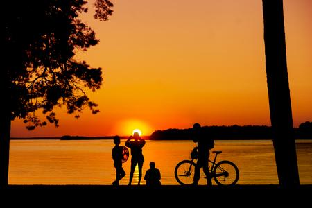 personas tomando agua: Montón de gente disfrutando de la puesta de sol sobre el agua y tomando fotos con el teléfono móvil