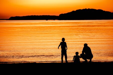 two children: Father with two children enjoying colorful sunset on beach