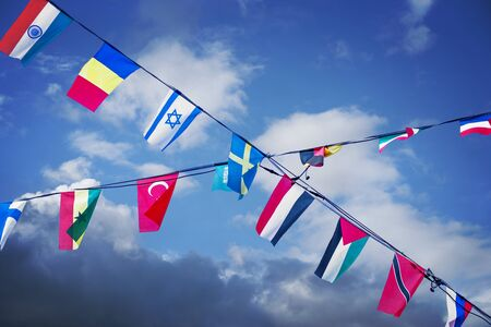 nation: many nation flags on blue sky, symbolizing unity and cooperation