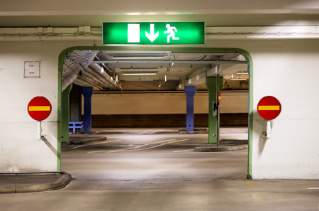 car park interior: Portal in multi-storey car park with one way signs and exit sign Stock Photo