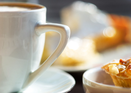 capuchino: Cerca de la taza de café capuchino con delicioso pastel Foto de archivo