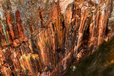 steep side of canyon with red rock and river at the bottom Stock Photo