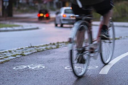 healthy path: Cyclist in blurred motion on cycling path by busy street at night