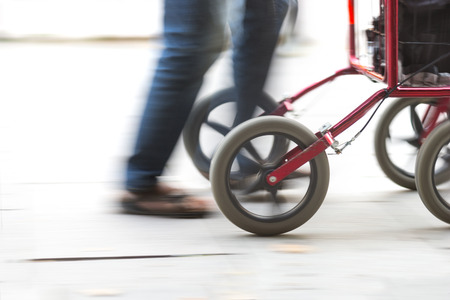 Feet of elderly person with red walking frame in blurred motion