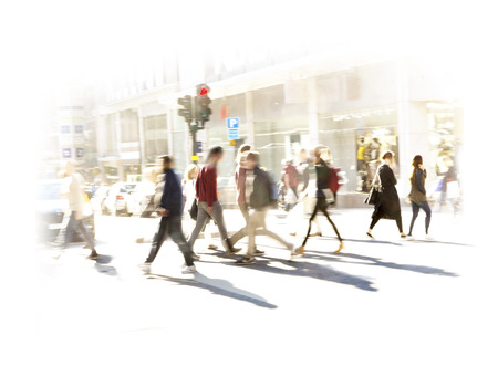 urban people: Crowd of people in blurred motion on pedestrian crossing at rush hour in bright sunshine Stock Photo