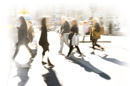 pedestrian crossing: Crowd of people in blurred motion on pedestrian crossing at rush hour in bright sunshine Stock Photo