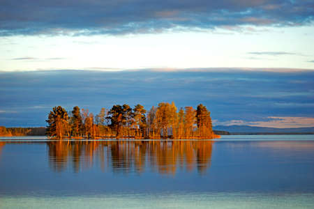 nature beauty: Scandinavian lake with island at sunset, reflected in the water