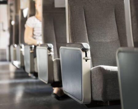 persona viajando: Fila de asientos en el tren, con el brazo de la mujer en el resto del brazo