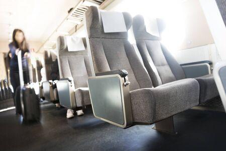 persona viajando: Fila de asientos en tren, mujer joven con la maleta en el movimiento enmascarado en el pasillo