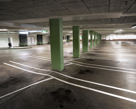 car park interior: Interior from empty indoor carpark with oil stains on floor and green columns