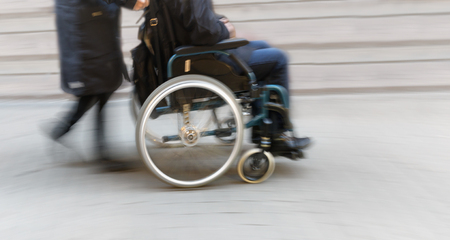 blurred: Man in wheelchair pushed by woman in blurred motion