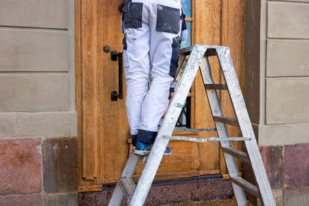 overol: Las piernas del hombre en overoles manchados blancos en escalera metálica