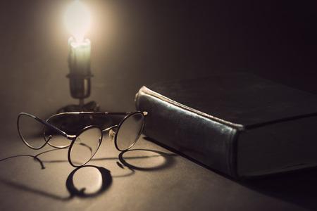literatura: Libro de la vendimia con los vidrios viejos y palillo de la vela con la vela encendida en el fondo