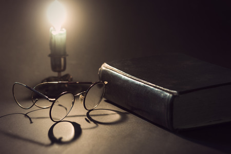 literatures: Vintage book with old glasses and candle stick with lit candle in background