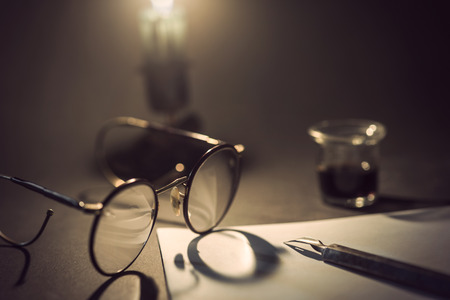 vintage paper: vintage ink pen on piece of white paper, old googles with shadow from candle light and jar of ink in background