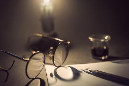 kugelschreiber: Vintage-Kugelschreiber auf weißes Stück Papier, alte googles mit Schatten von Kerzenlicht und Glas Tinte im Hintergrund