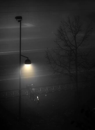 lamp post: bike lit by lamp post in dark foggy evening