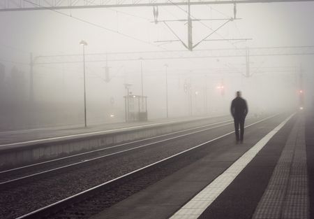 lonley: silhouette of man in blurred motion walking on platform, waiting for train on foggy day