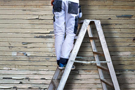 tatty: Legs of man in white stained overalls on metal stepladder, flaking old wooden wall in background
