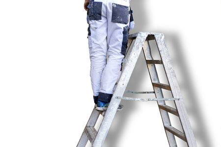 stepladder: Legs of man in white stained overalls on metal stepladder, white wall with shadow in background Stock Photo