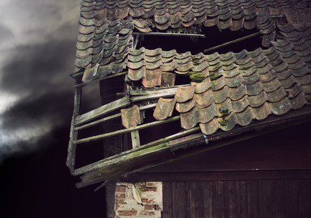 moody: Old wooden roof on collapsing building on dark moody evening sky